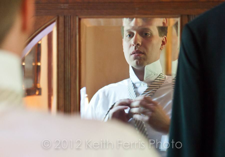 the groom putting on his necktie