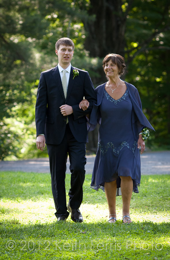The groom and his mother walk down the aisle