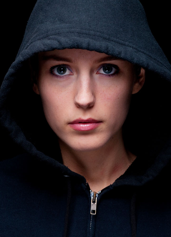 A young woman in a black hooded sweatshirt on a black background with low key lighting.