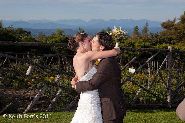 newlyweds kiss in front of the catskill mountain view at mohonk mountain house in new paltz ny