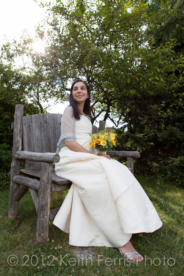 The elegant bride sitting on a bench in the garden